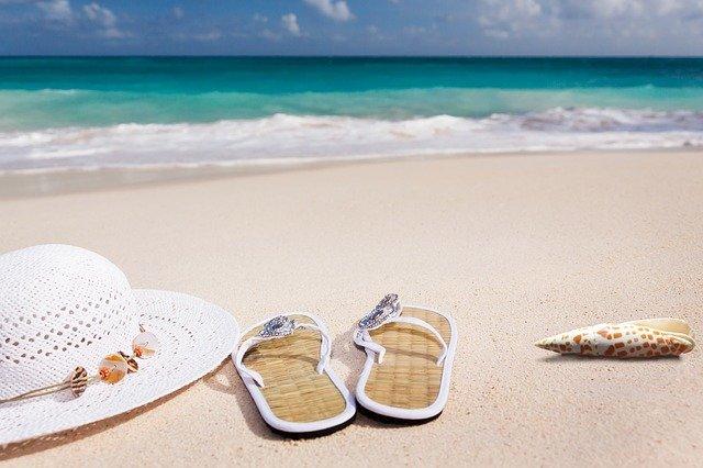 klobouk a pantofle na pláži